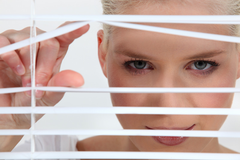 Woman peeping through blinds
