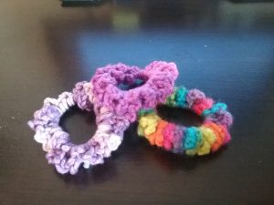 3 crocheted scrunchies in rainbow and purple colors