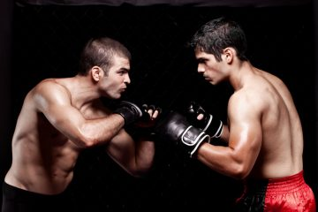 Two men wearing boxing gloves face off against each other