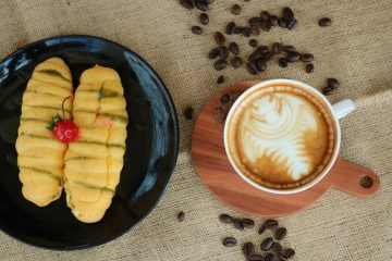 mug with coffee beside a plate with a pastry