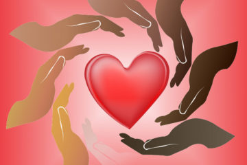 Hands in various skin tones surround a heart