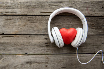 A red heart between white headphones
