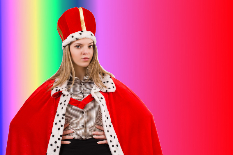 Woman in crown and cape in front of a multi-colored background