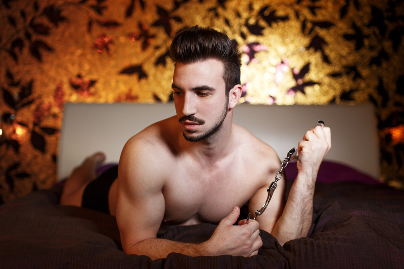 Bare-chested man on bed holding handcuffs