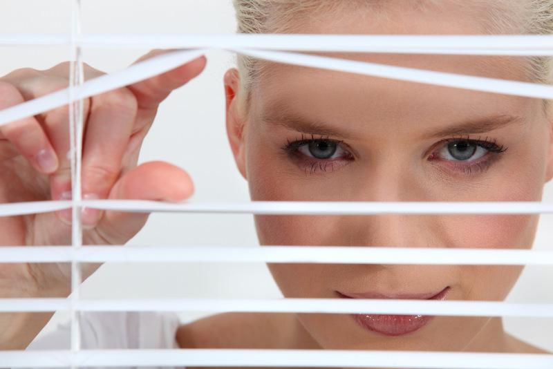 Woman peeping through blinds