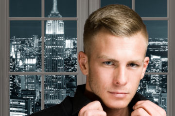 A handsome young blond man stands in front of a window showing New York City at night