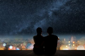 A couple is silhouetted under the stars