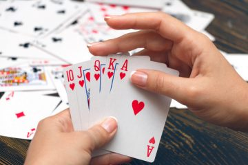 Well-conditioned female hands holding playing cards with poker strongest combination - royal flush