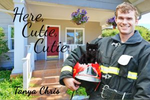 Male firefighter holding helmet with black kitten perched on top of it