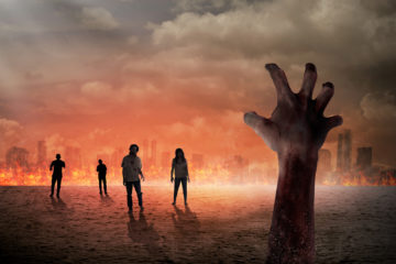 A menacing hand thrusts up from the ground as figures stumble across a barren landscape with burning buildings in the background