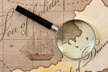 "An old fashioned map with a magnifying glass. The text ""Sea of Solitude"" and ""... of Desire"" can be read on the map"