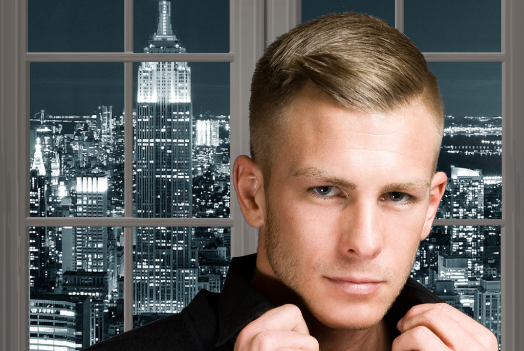 A blond man in front of a window showing a New York City night scene