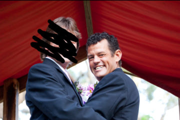 Two men in suits and boutonnieres holding each other but one has his face drawn over in black