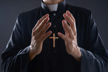 The torso of a man wearing a white collar and a wooden crucifix with his hands open in front of him